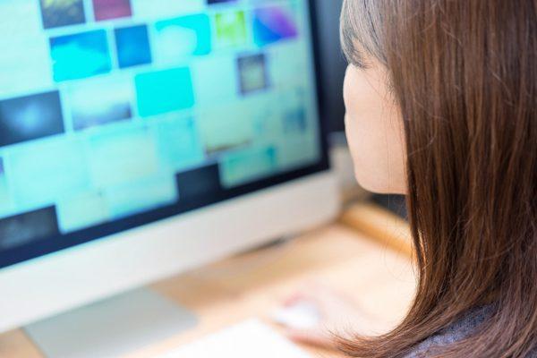 PC画面を見つめる女性